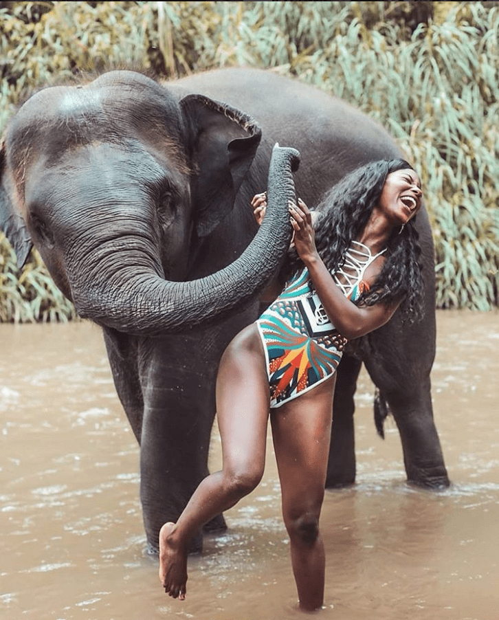 travel blogger DD plays with a baby elephant