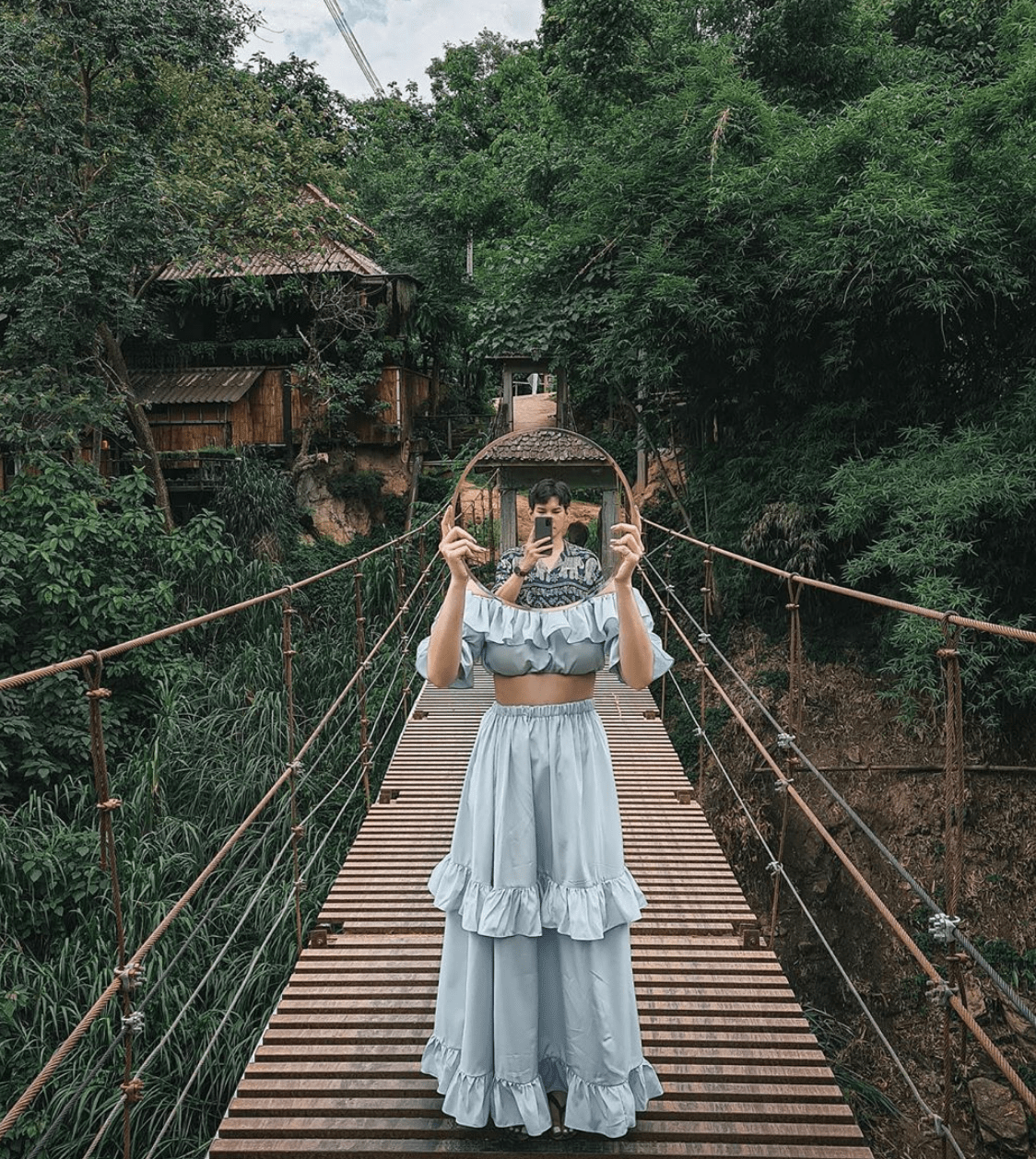 travel blogger on a jungle bridge