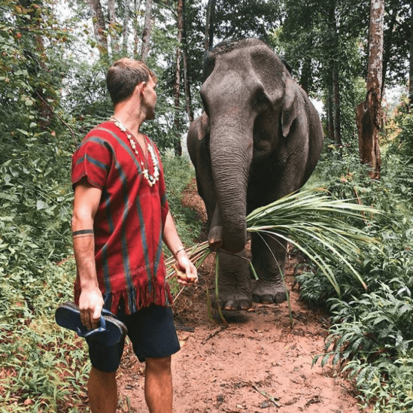 man hiking with an elephant
