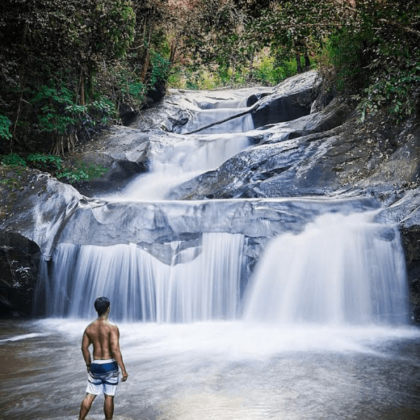 Man at jungle waterfall