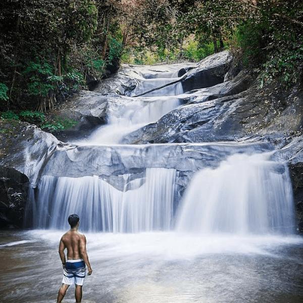 Man at jungle waterfall